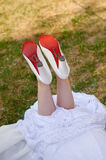 Bride lying on the grass with shoes Royalty Free Stock Photo