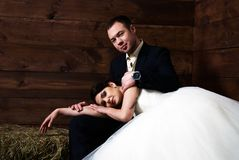 Bride lying on groom's lap in barn Stock Images