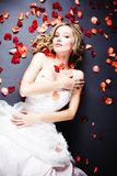 Bride lying among rose petals. Beautiful sexy bride lying on the floor among red rose petals on gray background Stock Photo