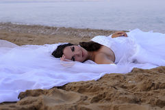 Bride. Lying on the sand at the beach Stock Images
