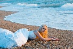 Bride lying at sea coast Stock Image