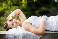 Bride lying on the wall in the park. Stock Photos