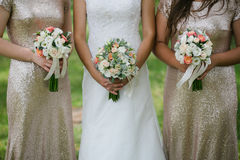 Bride and maids with flowers. Close up of bride and maids hands with flowers in their hamds Stock Photo