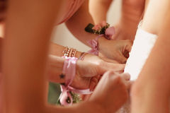 Bride maids help bride tie up her dress at the back Stock Photos