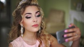 Bride makes selfie his phone. Stylish Woman Fiancee with Bridal Hairstyle, Event Makeup and Jewelry. stock footage