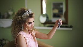 Bride makes selfie on phone. Stylish Woman Fiancee with Bridal Hairstyle, Event Makeup and Jewelry. stock video footage