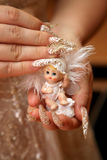 Bride with manicure holding a toy doll Stock Image