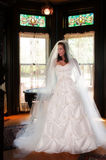 Bride in Mansion Before Wedding. Bride on staircase with stained glass window in back Royalty Free Stock Image