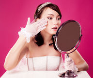 Bride with a mirror. Worried bride, sitting by the table with a mirror,  against pink studio background Stock Photo