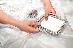 Bride with mirror. Bride hands holding vintage stile mirror Stock Image