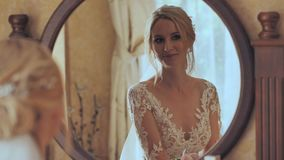 The bride at the mirror is preparing for the wedding. stock footage