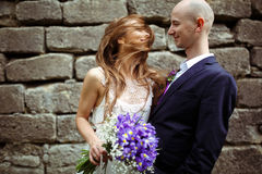 Bride mixes her hair around her face while groom holds her.  Stock Images