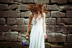 Bride mixes her hair around standing behind a stone wall.  Stock Image