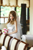 Bride mixes her hair and holds wedding bouquet in her arms.  Royalty Free Stock Photography