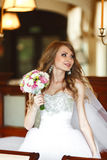 Bride mixes her hair and holds wedding bouquet in her arms.  Stock Photos
