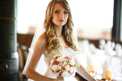 Bride mixes her hair and holds wedding bouquet in her arms.  Royalty Free Stock Photos