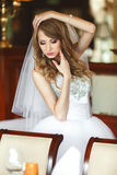 Bride mixes her hair and holds wedding bouquet in her arms.  Royalty Free Stock Images
