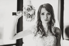 Bride mixes her hair and holds wedding bouquet in her arms.  Stock Image