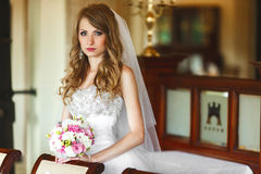 Bride mixes her hair and holds wedding bouquet in her arms.  Stock Images