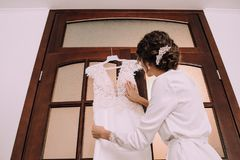 Bride morning dresses touches wedding dress. Bride in the morning dresses touches a wedding dress Royalty Free Stock Photo