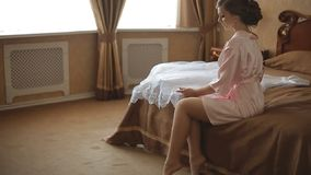 Bride in the morning in a transparent lace dress and underwear and stockings. Bride in the morning in transparent lace dress and underwear and stockings stock video footage