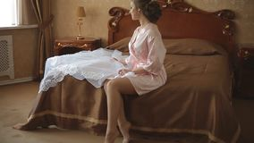 Bride in the morning in a transparent lace dress and underwear and stockings. Bride in the morning in transparent lace dress and underwear and stockings stock footage