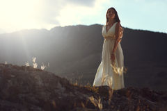 Bride in the mountain sunset light. A beautiful young bride posing on top of  mountain in sunset light Stock Photos