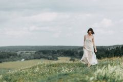 Bride in the mountains. The bride in a light dress flying in the mountains, with a bouquet and the arch. Wedding cake and floral Stock Photography