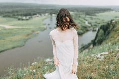 Bride in the mountains. The bride in a light dress flying in the mountains, with a bouquet and the arch. Wedding cake and floral Royalty Free Stock Photography