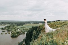 Bride in the mountains. The bride in a light dress flying in the mountains, with a bouquet and the arch. Wedding cake and floral Stock Photo