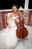 Bride musicial playing cello. Bride musicial with warm smile and beautiful eyes playing cello Royalty Free Stock Photo