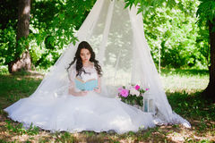 Bride on the nature of reading a book, decor, peonies, flowers, lifestyle, marriage, family, love Royalty Free Stock Photography