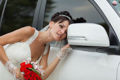 Bride near the car. Attractive bride looks in rearview mirror of wedding car stock images