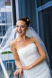 Bride near the glass wall. Stock Image