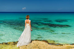 A bride on an ocean shore. A bride in a white dress is standing on a shore and staring at the ocean stock photos