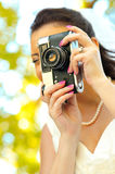 Bride with old retro camera taking pictures Royalty Free Stock Photography