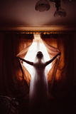 Bride opens dark curtains letting the light go Stock Photo