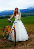 Bride on orange bike in beautiful wedding dress with lace in landscape. Royalty Free Stock Photos