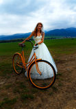 Bride on orange bike in beautiful wedding dress with lace in landscape. Stock Photos
