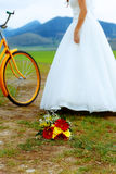 Bride on orange bike in beautiful wedding dress with lace in landscape. with wedding bouquet. wedding concept. Royalty Free Stock Image