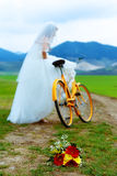 Bride on orange bike in beautiful wedding dress with lace in landscape. with wedding bouquet. wedding concept. Stock Photo