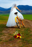 Bride on orange bike in beautiful wedding dress with lace in landscape. with wedding bouquet. wedding concept. Stock Photos