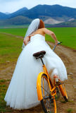 Bride on orange bike in beautiful wedding dress with lace in landscape. wedding concept. Stock Photo