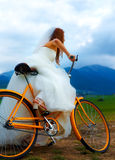 Bride on orange bike in beautiful wedding dress with lace in landscape. wedding concept. Royalty Free Stock Image