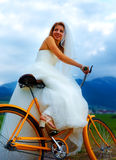 Bride on orange bike in beautiful wedding dress with lace in landscape. wedding concept. Royalty Free Stock Photo