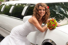 Bride with original bouquet leaning on a white car Stock Photo