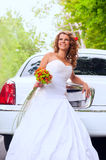 Bride with original bouquet near the white car. Smiling buxom bride with original bouquet in her hand standing in front of the white car Stock Photography