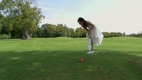 Bride on outdoor background. Woman hitting apple with umbrella. Golf for ladies. Strike with precision stock video footage