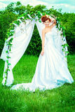Bride outdoor. Beautiful bride with chaming red hair stands under the wedding arch. Wedding dress and accessories. Wedding decoration Stock Photo