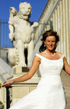 Bride outdoors. In front of a lion statue Royalty Free Stock Photo